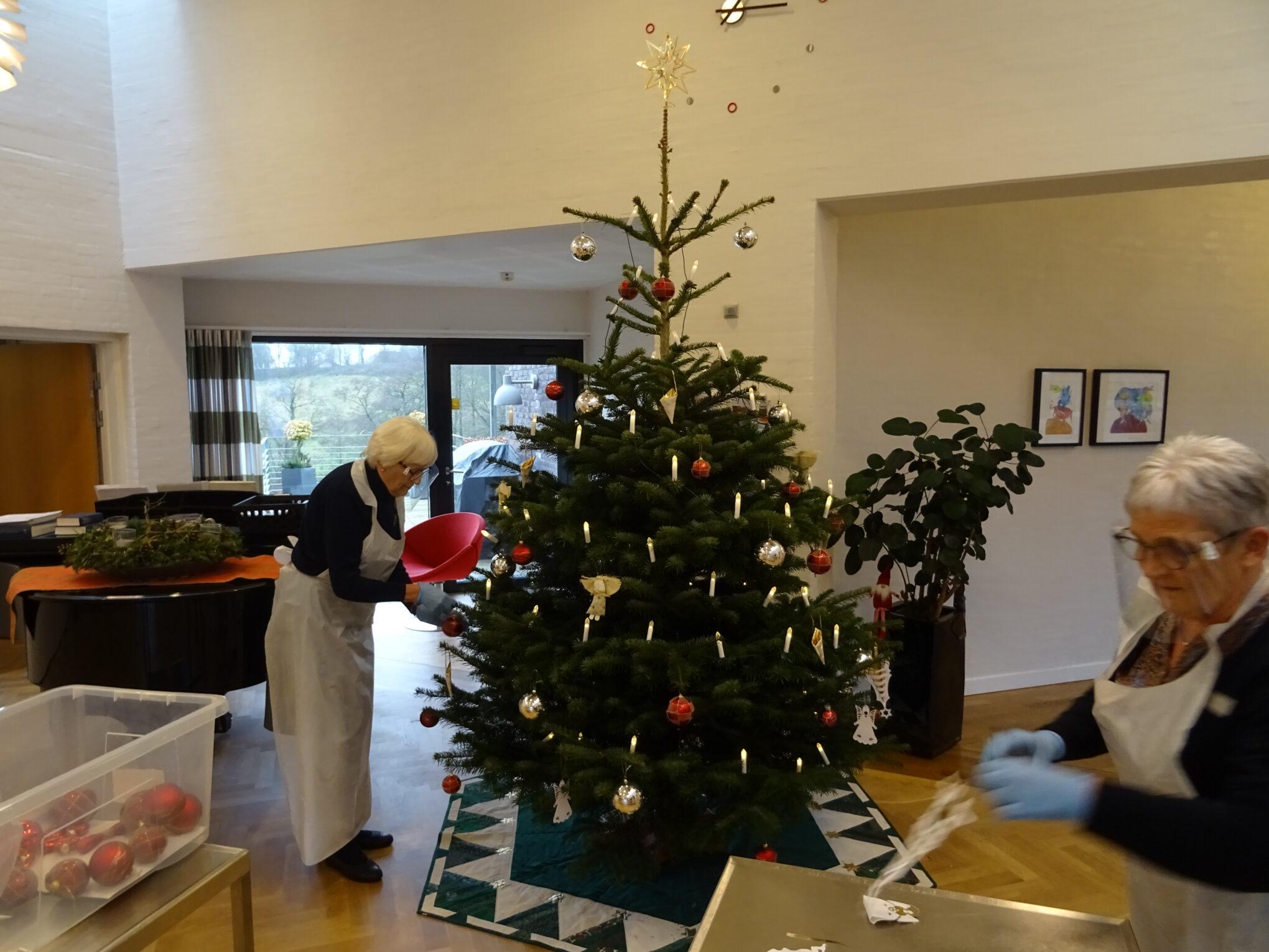 Juletræet bliver pyntet af frivillig Birthe og Gertrud